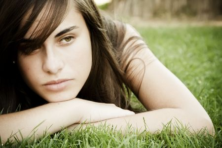 pensive woman: Young thoughtful woman laying on the grass