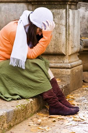 tormented: Young thoughtful woman sitting in stone stairs.