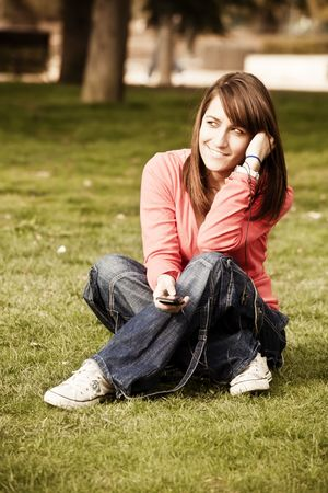 Young beauty listening music on the grass photo