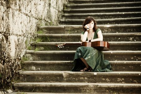 Young beautiful music performer posing with her guitar Stock Photo - 4747752