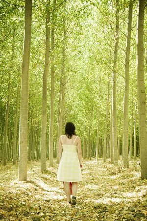walking path: Young woman walking through the woods.