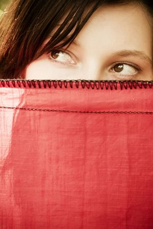 Young curious woman spying behind veil photo