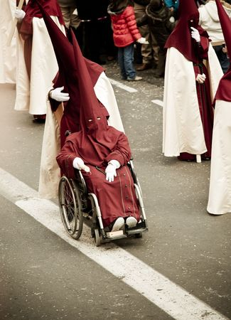 Disabled believer in a procession over the streets.