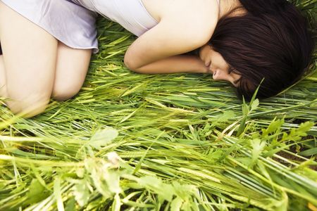 Beautiful girl sleeping over the grass photo
