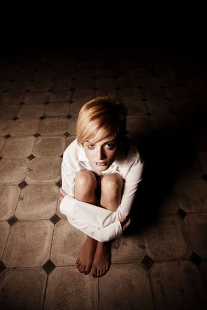 woman prison: Young blond woman alone in the darkness