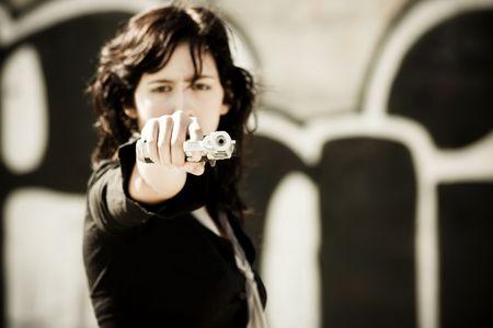 assasin: Young woman aiming at the camera. Focus in the gun barrel. Stock Photo