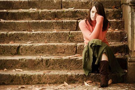 mujer pensativa: Joven mujer sentada en serio escaleras de piedra.
