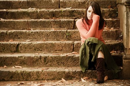 sad old woman: Young thoughtful woman sitting in stone stairs.