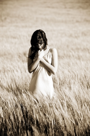 timid: Sad young woman on meadow. Stock Photo
