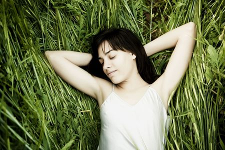 lay down: Young beautiful woman sleeping over the grass