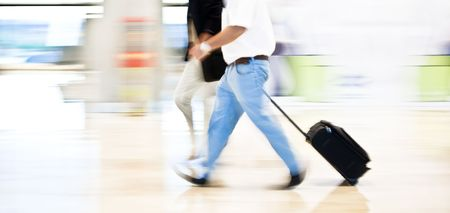 quickly: Two business men moving quickly on the terminal. Panning technique. Stock Photo