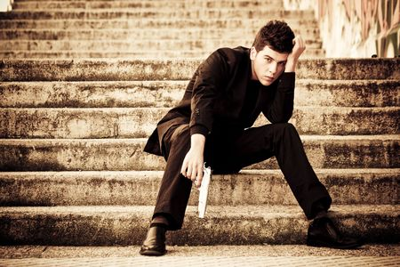 Young armed man waiting on the steps Stock Photo - 5183526