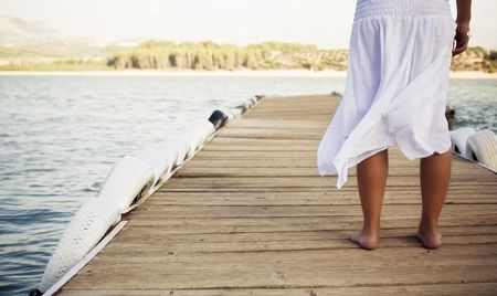 the mooring: Young shoeless woman on pier .