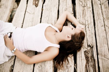 Young woman laying over wooden surface photo