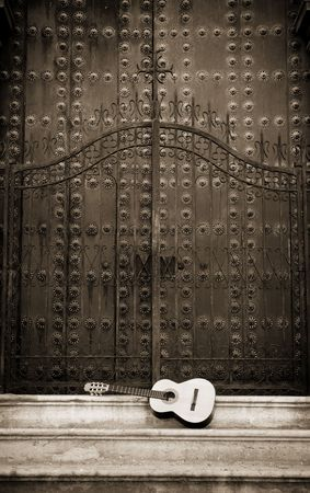 Spanish guitar in front of a cathedral doors photo