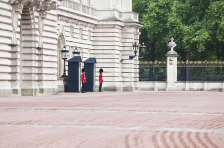 beefeater: Buckingham palace entrance with two guards.