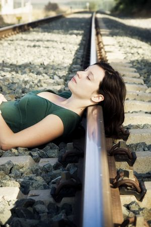 unintelligent: Young woman laying on a railway.