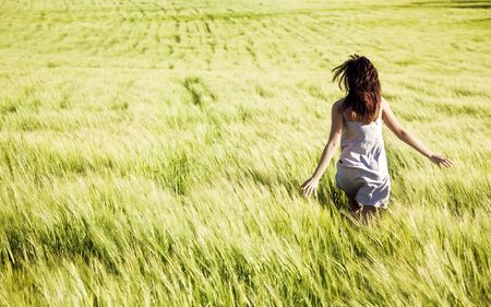 Young girl running on a green field photo