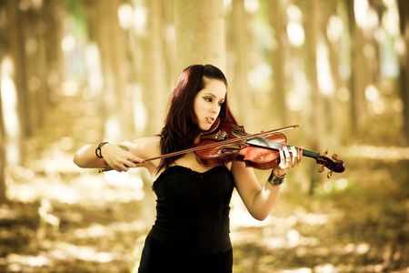 Young beautiful gothic girl playing violin over nature background. photo