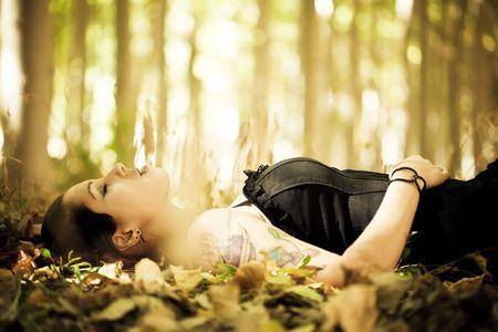 dode bladeren: Mooie gothic meisje leggen over de bladerdek. Stockfoto