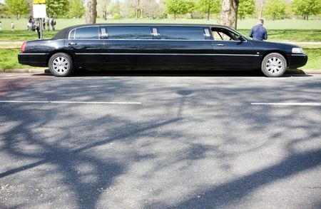 Unrecognizable limo driver waiting in a park. photo