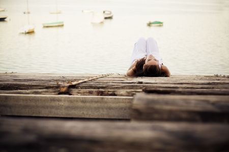 pensive woman: Young pensive woman over wooden surface near the water Stock Photo