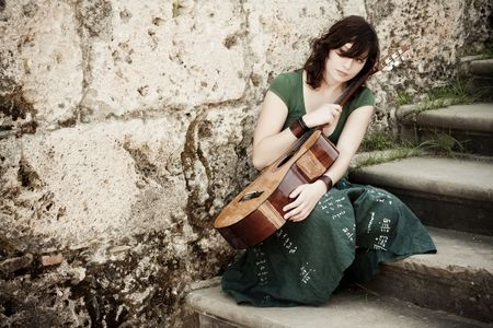 Young female guitarist on antique background Stock Photo - 5826989