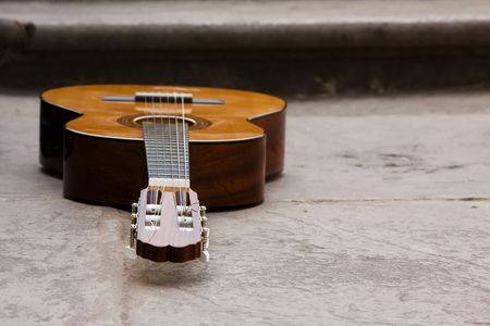 Classic guitar on the ground, focus on bridge