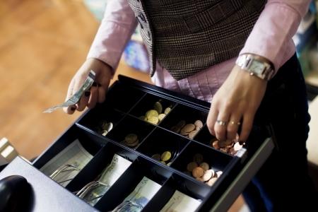 cassettiera: Donna mani sul registro di cassa negozio. Fatture e monete in euro.