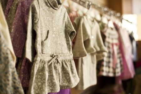 Clothes for little girls in a fashion shop. Shallow focus. photo