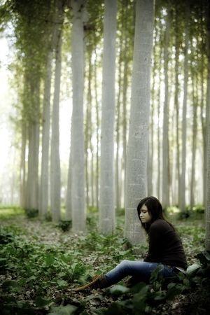 Young beautiful thoughtful girl sitting on the forest photo