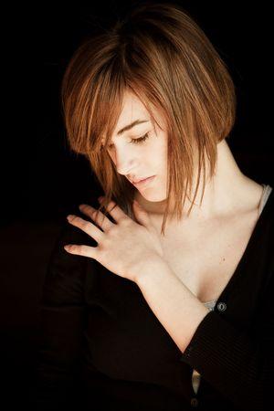 Sad blond woman portrait against black background photo