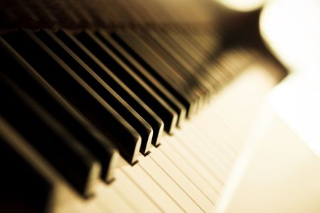 acoustically: Piano side view with keys lost in the light.