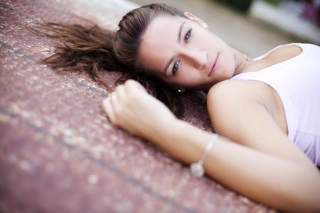 Young woman laying over rusty surface. photo