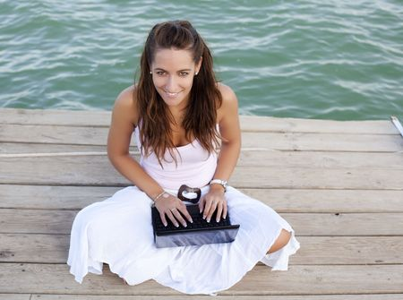 Woman working on laptop on pier photo