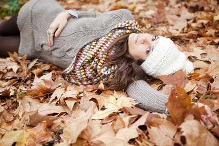 Staring young beautiful brunette girl in autumn background photo
