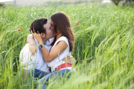 Young lässig paar auf ein Weizenfeld zu küssen.  Lizenzfreie Bilder