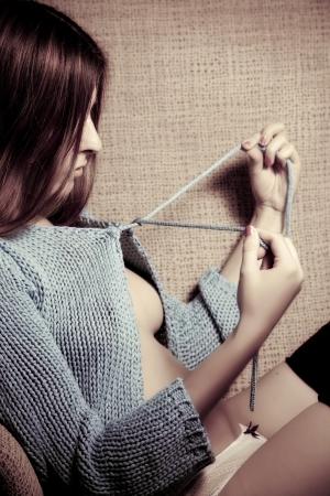 Young beautiful woman undoing her cardigan. photo