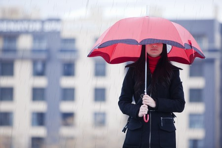 is raining: Young girl hidden under umbrella while it�s raining Stock Photo