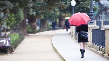 lloviendo: Chica joven detrás de paraguas mientras it?s lloviendo