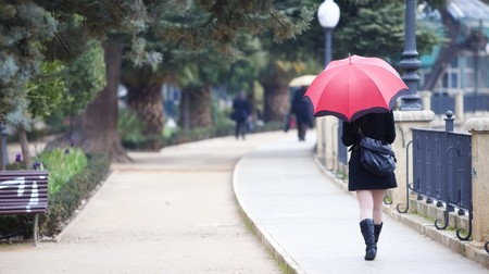 street shot: Young girl behind umbrella while it�s raining Stock Photo