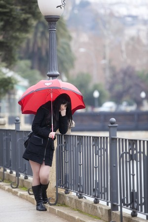 Sad girl with red umbrella on urban background. photo