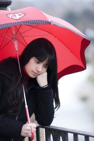 Sad girl with red umbrella with pensive gesture. photo