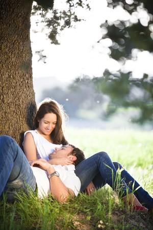 Junge schöne Paar ruhelosigkeit unter einem Baum