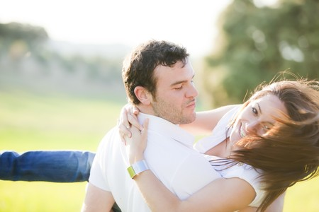 Young beautiful playful couple in action. Focus on him. Stock Photo - 6965699