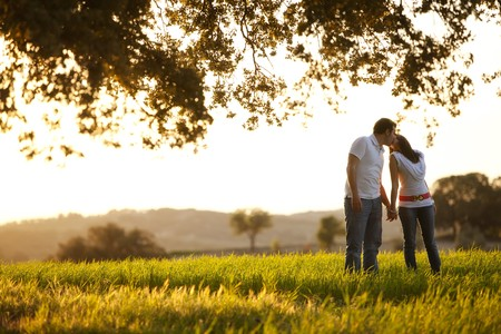man woman kissing: Young kissing couple on idyllic background