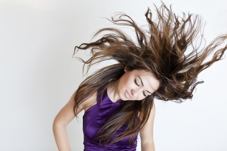 Young beautiful girl with windy hair over white background. photo