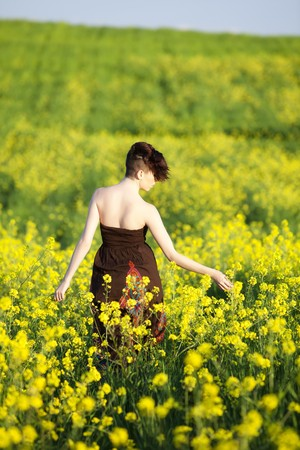 Young girl gathering flowers in a yellow flowers field. photo