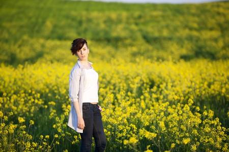 Young beautiful girl posing on a yellow field. photo