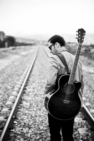 black and white railroad tracks: Lone handsome male musician on his way Stock Photo